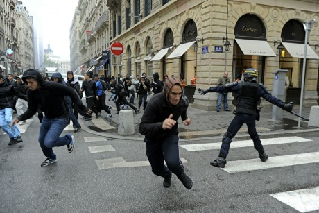 French Youth run from riot police forces during clashes on October 20, 2010 on the sideline of anti pensions reform protests in Lyon. (PHILIPPE DESMAZES AFP Getty Images)